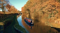 Autumn exterior narrow boat sailing on canal Stock Footage