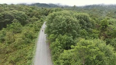 Aerial view of a motorbike riding on road through primary montane rainforest Stock Footage