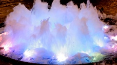 The water in the fountain bubbling in multi-colored rays of light. Stock Footage