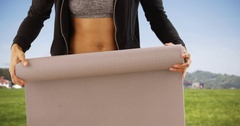 Portrait of healthy black woman rolling yoga mat. Stock Footage