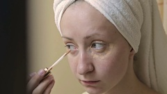 Young, pretty woman applying concealer on her eyelid in bathroom Stock Footage