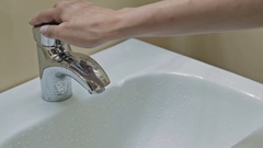 Bathroom tap turning on, running and turning off Stock Footage