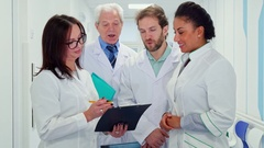 Medical team looks at clipboard Stock Footage