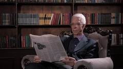 Portrait Of Happy Mature good looking Man Reading Newspaper in glasses in Stock Footage