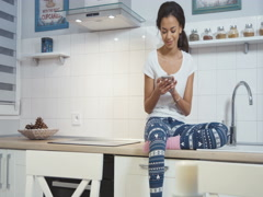 Young Afro American woman sitting in a kitchen and writting on mobile phone. Stock Footage