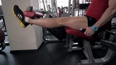 Young adult man doing leg extension workout exercise in gym Stock Footage