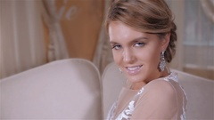 Beautiful smiling bride woman with long stylish hair posing in wedding dress at Stock Footage