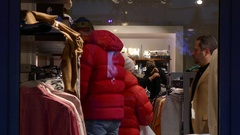 Crowd of people shopping cloths in store trying on suit coat and jacket Stock Footage