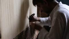 Carpet weaving. Man weaves a carpet Kashmir at weaving factory . Srinagar, India Stock Footage