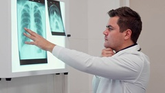Male doctor holds his hand on the x-ray image Stock Footage