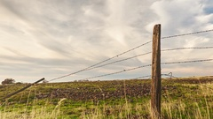 Time Lapse of Clouds Passing over a Broken Barbwire Fence. Stock Footage
