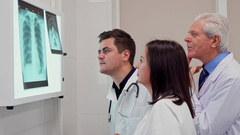 Medical team analizes x-ray on x-ray view box Stock Footage