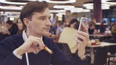 Young men using smartphone eat fried chicken wings at food court in shopping Stock Footage