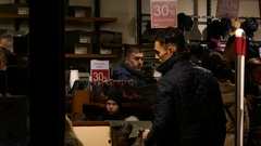 Crowd of people shopping going in and out of small shoe store black Friday sale Arkistovideo