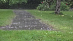 Heavy rain water drops falling on garden stone pavement and splashing in rainy Stock Footage