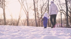 Happy woman and child playing with snow in winter park. Stock Footage