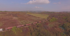 Cargo train runs through the fields. Railway wagons for hazardous materials Stock Footage