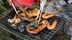 The hands are grilled Seafood grill or  barbecue with charcoal in the party. Stock Footage