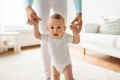 Happy baby learning to walk with mother help Stock Photos