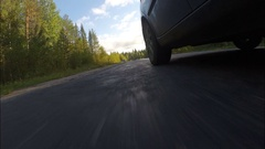 The car goes on the road passing through the forest. Stock Footage