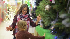 Mother and Child Choosing Christmas tree in the Supermarket. Young Beautiful Mom Arkistovideo