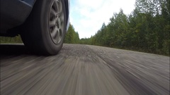 The road in the forest. The car rides on the old road in the fall. Stock Footage