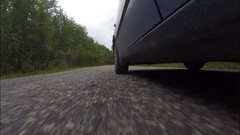 The car rides on the cracked road, built in the woods. Stock Footage