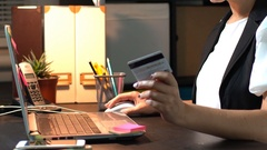 Online shopping female hand holding a  credit card and shopping online Stock Footage