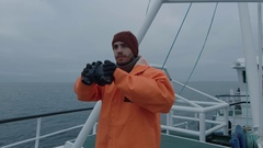Captain of Commercial Fishing Ship Dressed in Protective Coat Looking through  Stock Footage