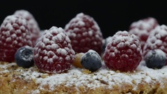 Cake with raspberries, blueberries, sea buckthorn sprinkled with powdered sugar Stock Footage