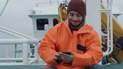 Casualy Dressed Fisherman Using Mobile Phone while Traveling on Ship. Stock Footage