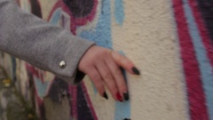 Woman's hand with red nails touching concrete wall Stock Footage