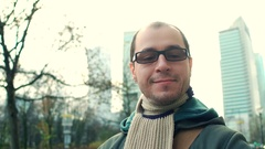 Cheerful programmer wearing black rim glasses walks on city business street. 4K Stock Footage