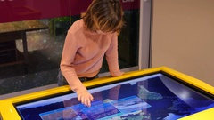 Woman typing sliding an educational geographical multimedia touchscreen display Stock Footage