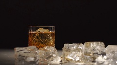 A piece of ice in a glass of whiskey.Dark, light and shadows Stock Footage