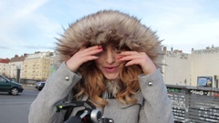 Young beautiful girl in winter jacket with fur hood outdoor Stock Footage