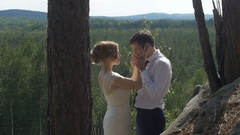 The bride and groom fondly hugging in the park Stock Footage