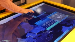 Woman typing sliding an educational geographical multimedia touchscree display Stock Footage