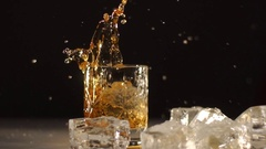 An ice ball falling down into glass with wiskey. Drink is spleshing on the sides Stock Footage