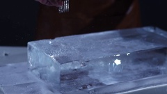 The barman crushing ice with special fork and breaking off a big piece of ice Stock Footage