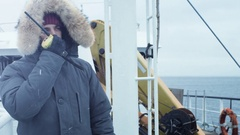 Adventurer in Warm Jacket Standing on Ship and Using Radio for Communication.  Stock Footage