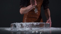 Barman with strong arms crushing ice with special fork and breaking off a big Stock Footage