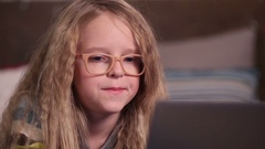 Beautiful little girl using computer in bedroom Stock Footage
