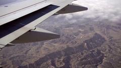 Airplane wing passenger view of mountains below - aerial of Santa Cruz Stock Footage