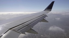 Airplane passenger view with wing flying over clouds and Northern California Stock Footage