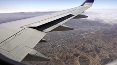 Mountains and clouds and wing of plane from airplane window in flight Stock Footage