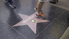 People walking over Bruce Willis star, man daughter on Hollywood Boulevard LA Stock Footage