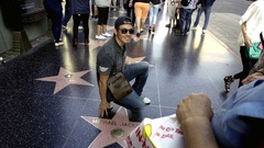 Man with sunglasses posing over Michael Jackson star on Hollywood Walk of Fame Arkistovideo