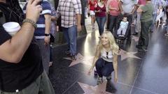 Blonde woman tourist kneeling photo Michael Jackson star Hollywood Boulevard LA Stock Footage