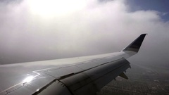 Airplane wing flying through cloudy sky over Northern California city Stock Footage